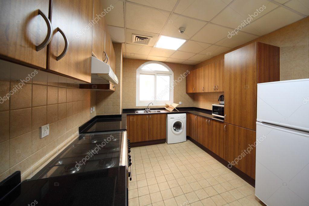 cucina con armadi marrone, lavatrice, fornello e frigorifero — Foto ...