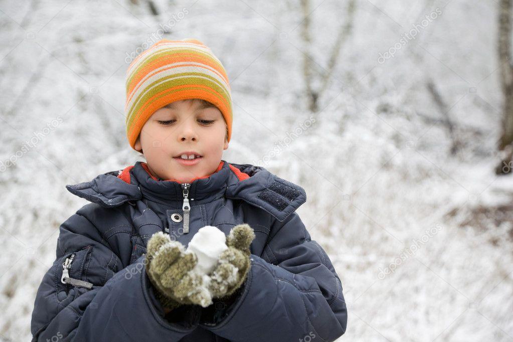 Boy keeps in hands snowball in wood in winter