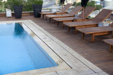 Arranged chairs next to swimming pool