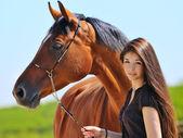Fotografie junges Mädchen und Bucht Pferd