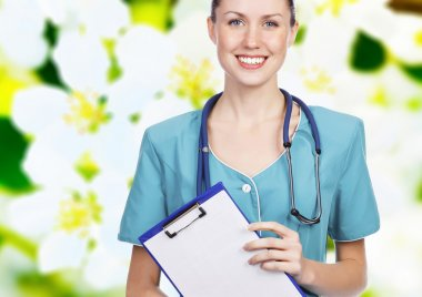Smiling female doctor holding a clipboard against flower backgro