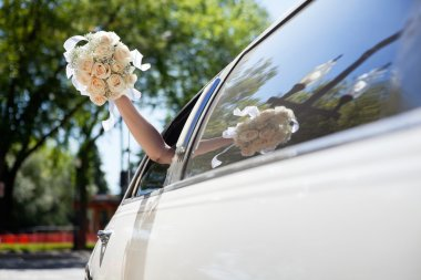 Bride waving hand holding bouquet