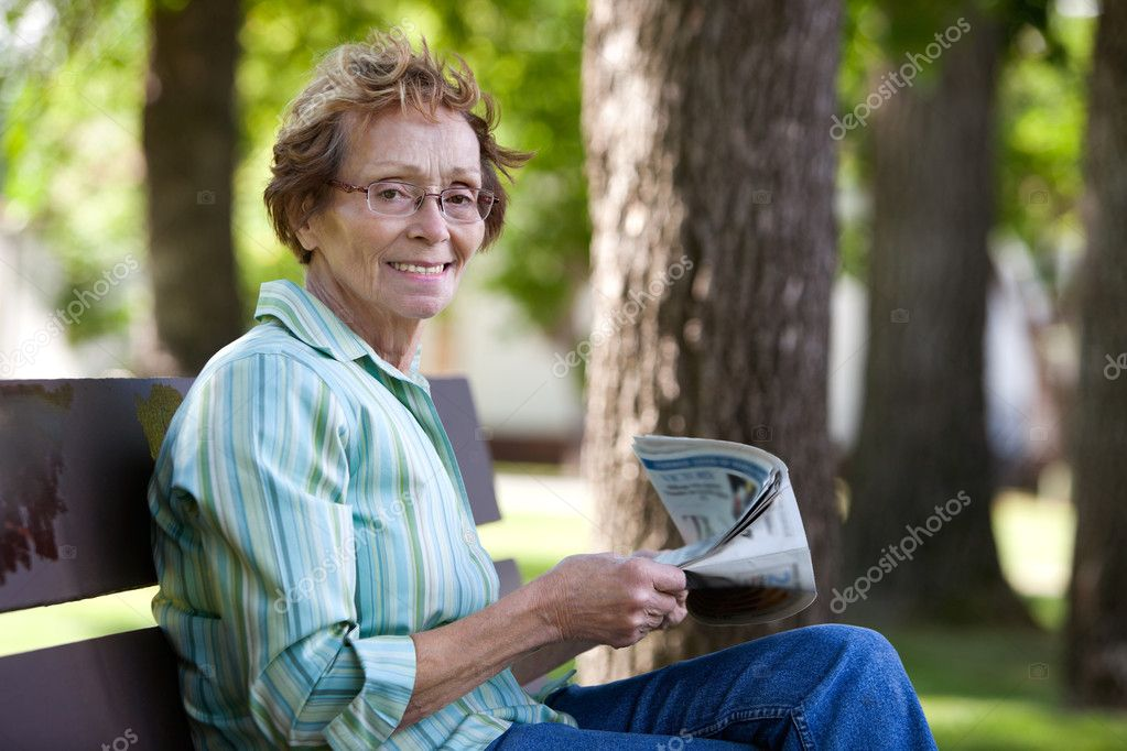 Woman reading newspaper in park