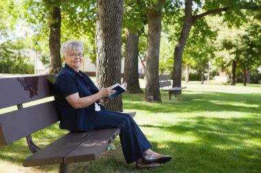 Woman reading book in a park