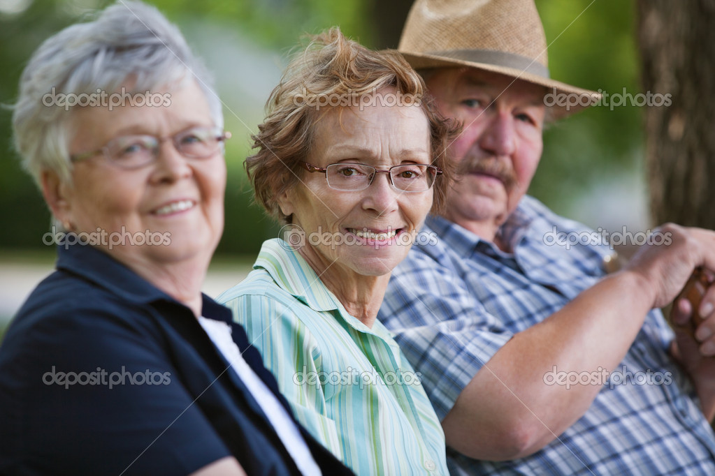 Senior friends sitting together in park