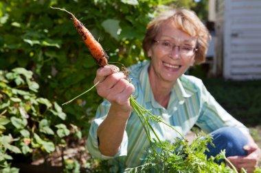 Senior woman holding carrot