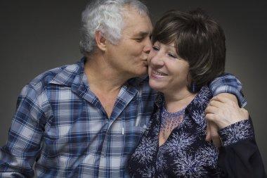 Older couple: elderly man kisses the old woman - love concept