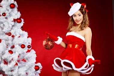 Beautiful young woman in Santa Claus clothes holding presents ov