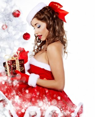 Fashionable young woman in Santa Claus clothes with presents