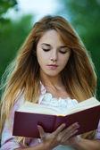 Fotografie junge Frau liest rotes Buch