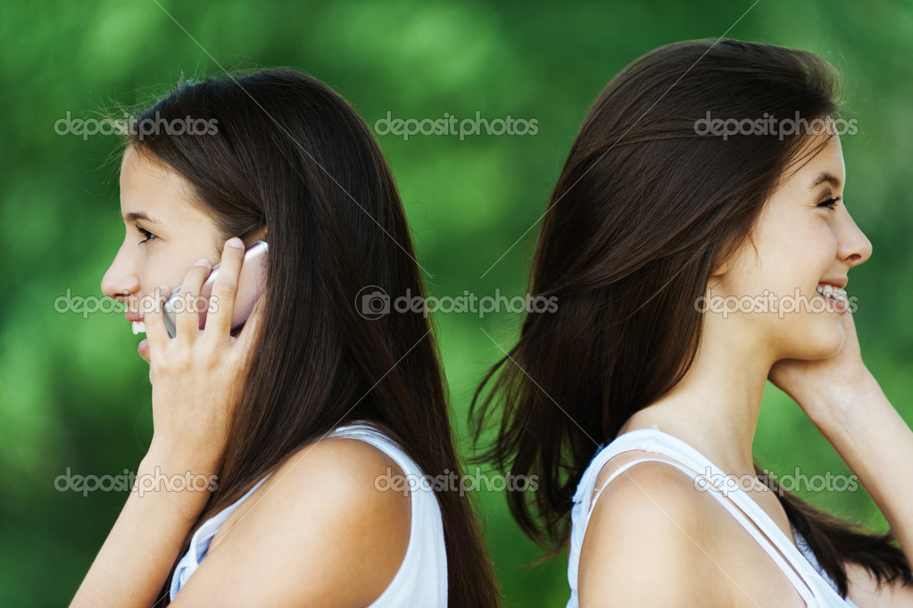 Two woman profile talk phone