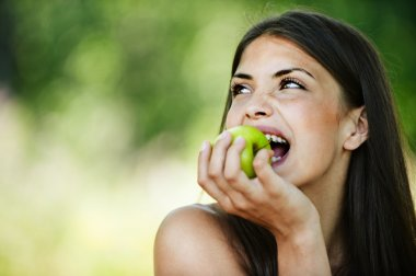 Portrait young charming woman biting apple
