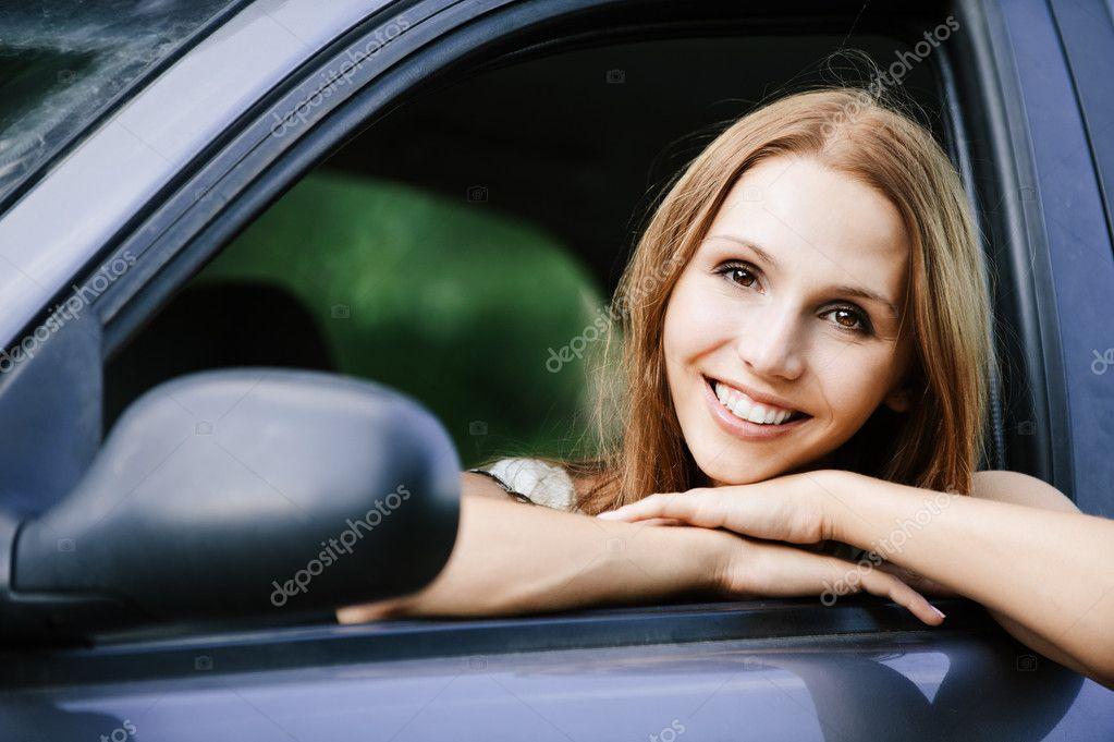 Young beautiful young woman sitting car