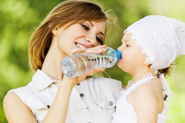 Young charming caring mother gives daughter drink