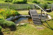 Malé zahradní jezírko s dřevěným mostem