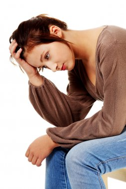 Sad teenage girl in depression thinking and touching her head.