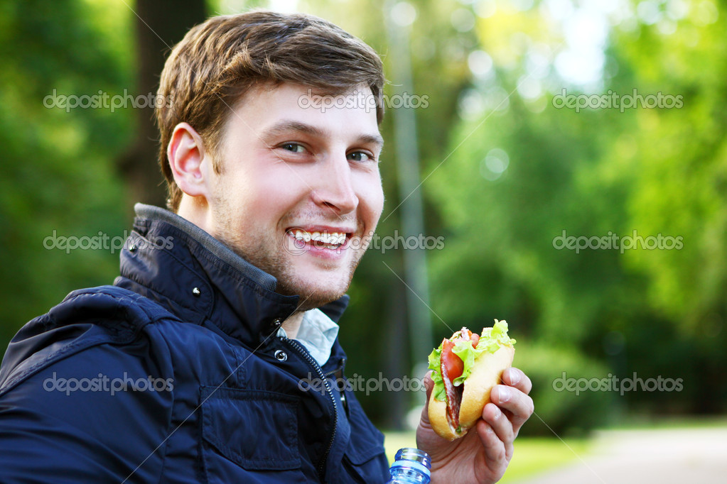 Young man relaxies in the park at lunch time