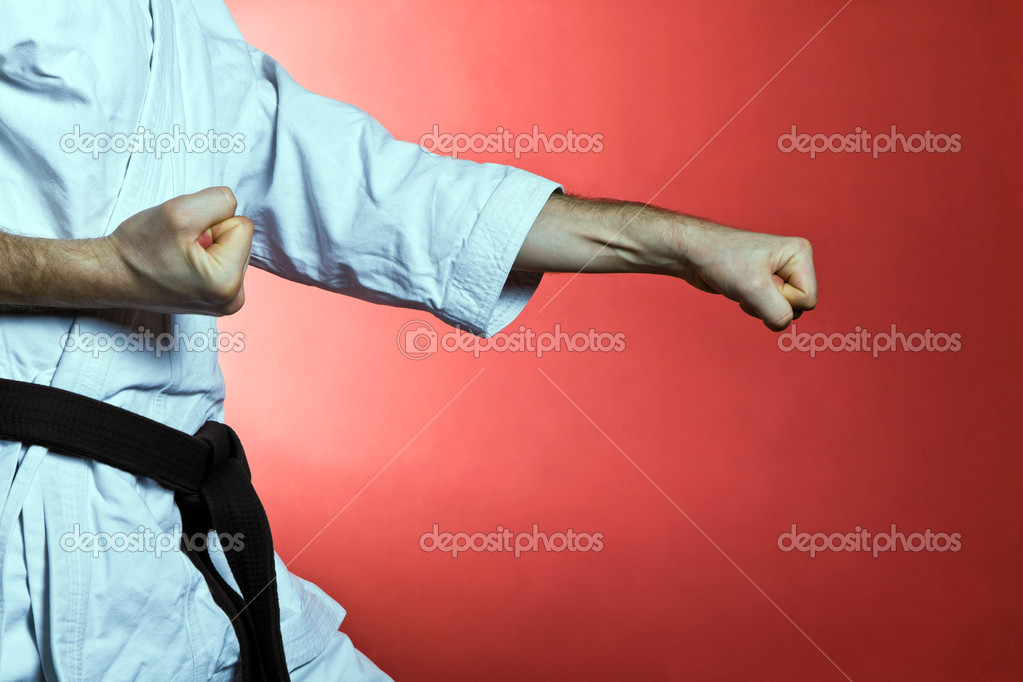 Young man practicing karate over red background stock vector