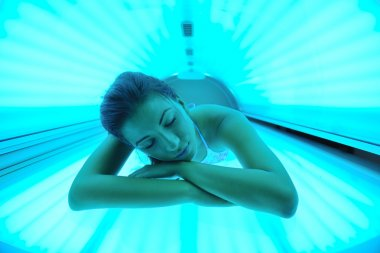Beautiful young woman tanning in solarium