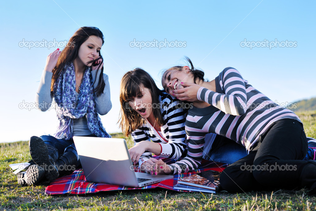 Group of teens working on laptop outdoor