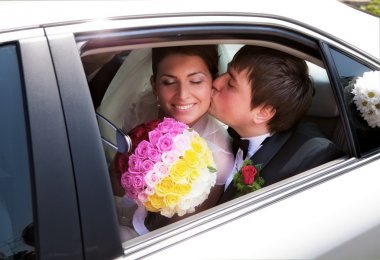 Closeup of newlywed couple kissing in wedding car