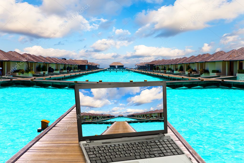 Wooden road over the sea and the laptop with a beach picture