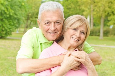Happy elderly man embracing mature woman