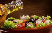 Fotografia insalata di verdure con olio doliva, versare da una bottiglia