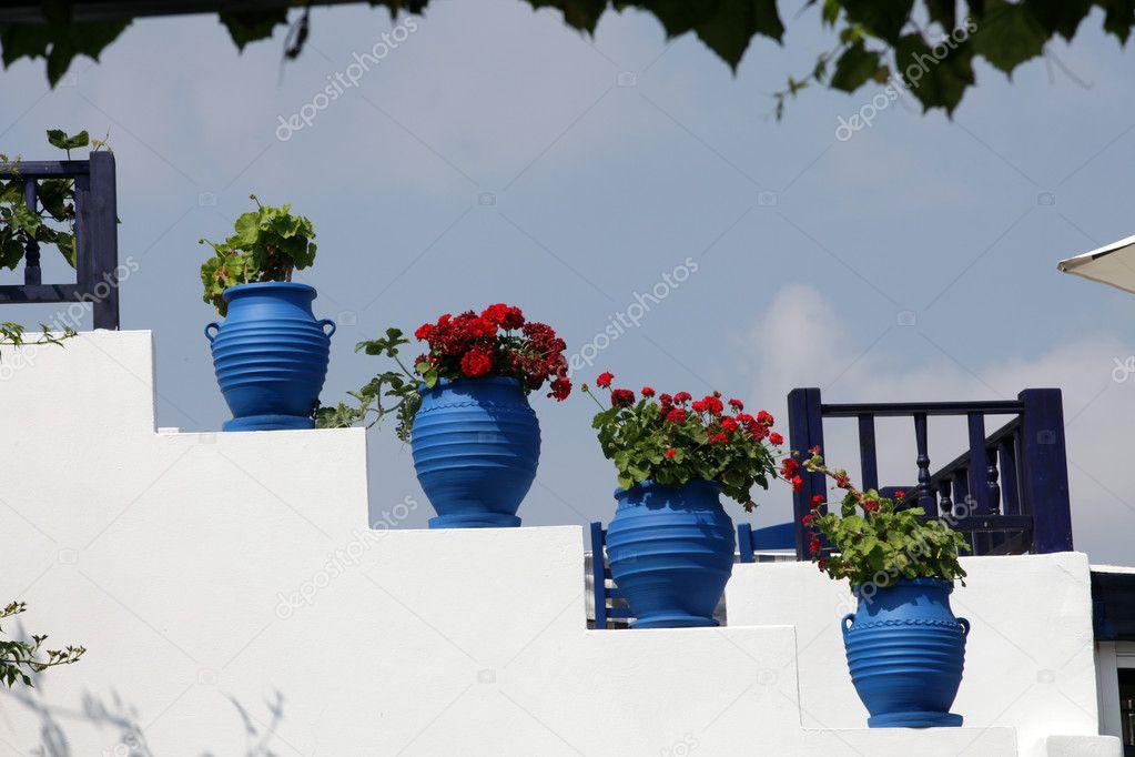 Witte trap versierd met rode bloemen in blauwe potten zia eiland