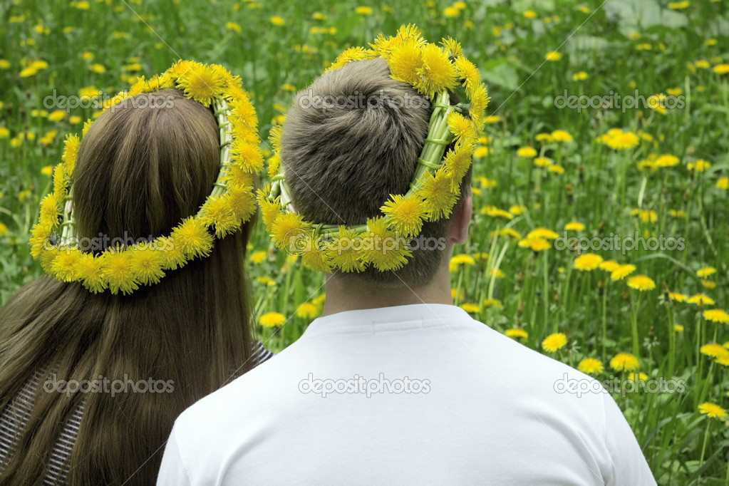 Loving couple in wreaths from dandelions