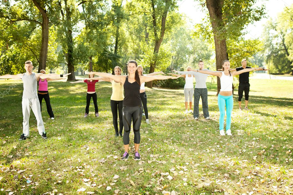 Large group exercising in park