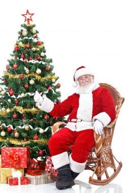 Santa sitting next Christmas tree