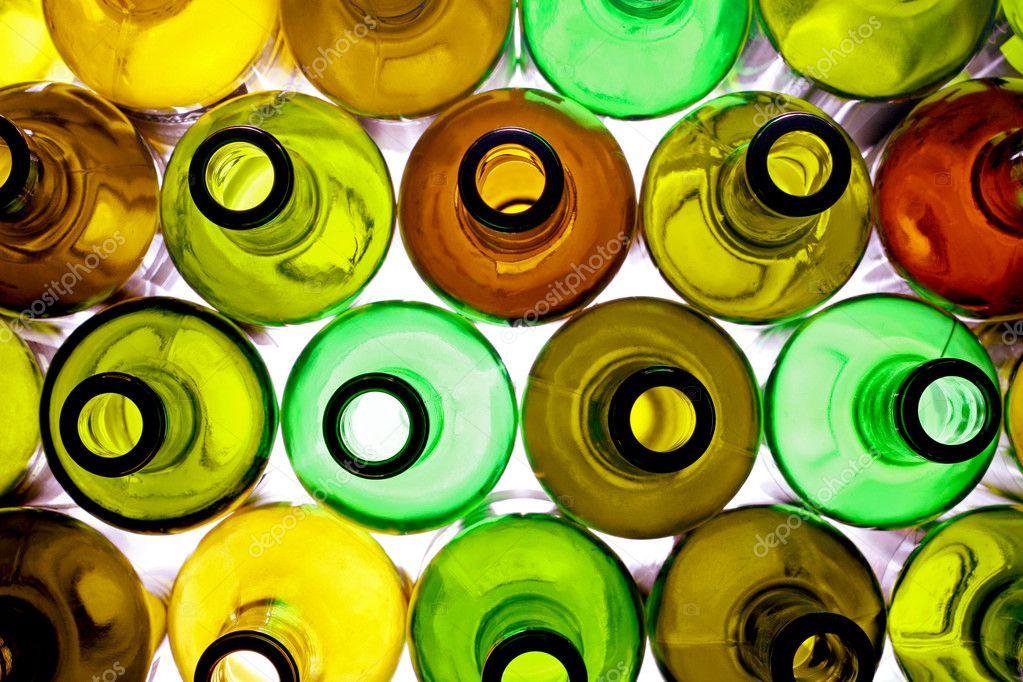 Stack of assorted empty wine bottles backlited