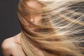 Wellness a spa. Smyslná žena model s rozcuchaný létající tmavě blond vlasy