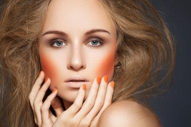 High fashion look. Woman model with fashionable makeup, bright orange blush