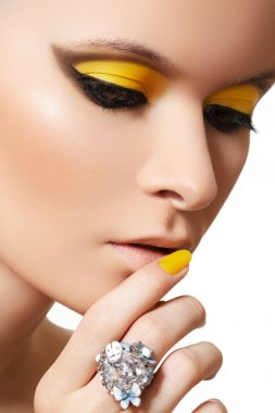 Close-up portrait of beautiful model face with neon bright yellow make-up