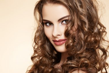 Lovely model with shiny volume curly hair. Pin-up style on beige background