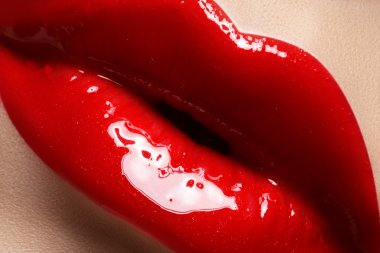 Close-up of woman's lips with bright fashion red glossy make-up