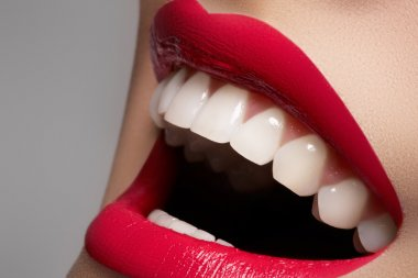 Close-up happy female smile with healthy white teeth, bright magenta lips