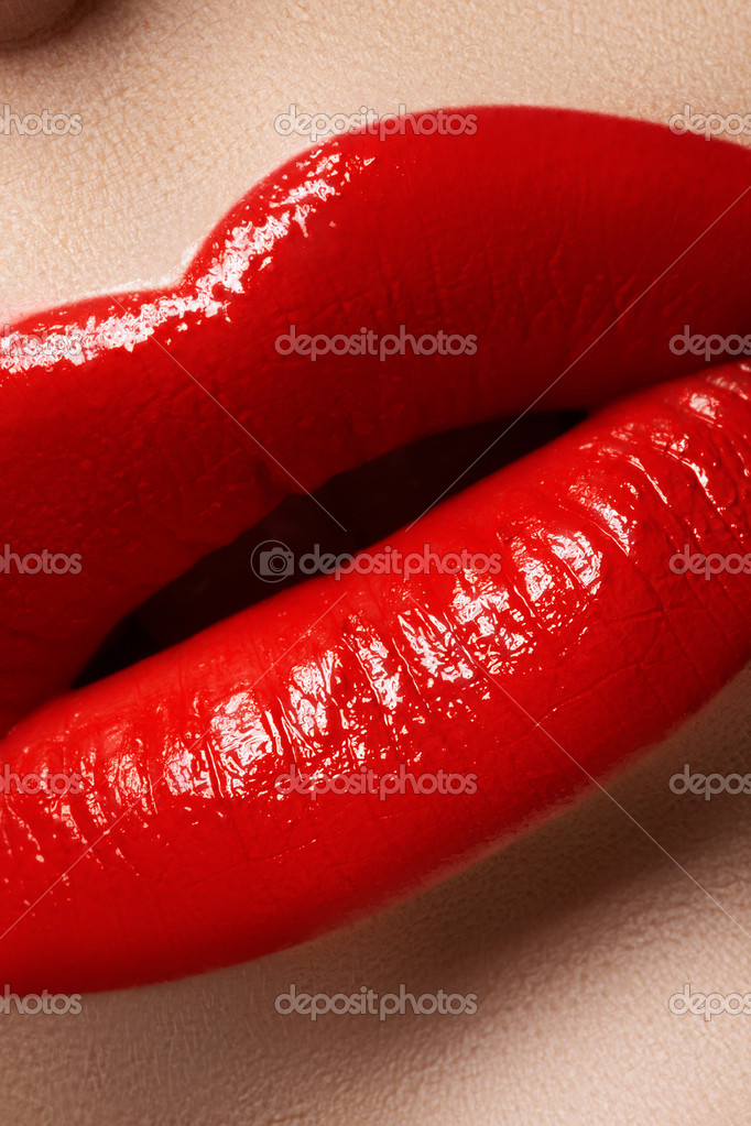 Close-up of woman's lips with bright fashion red makeup. Macro lips