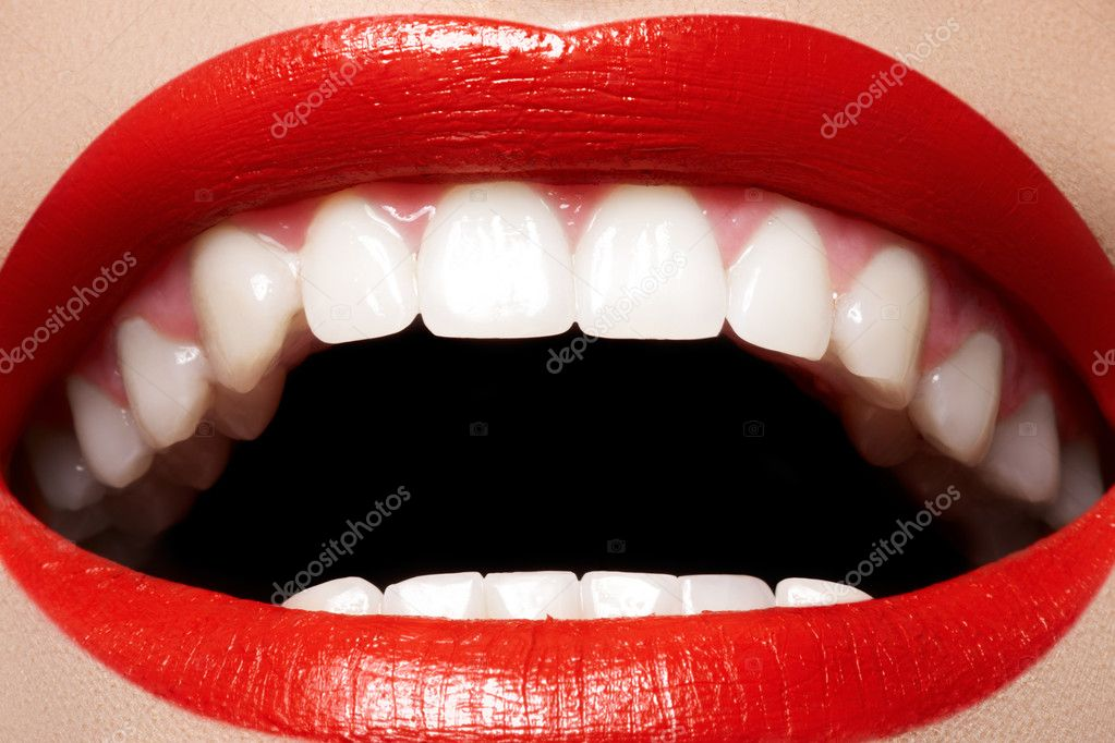 Close-up happy female smile with healthy white teeth, bright red gloss lips