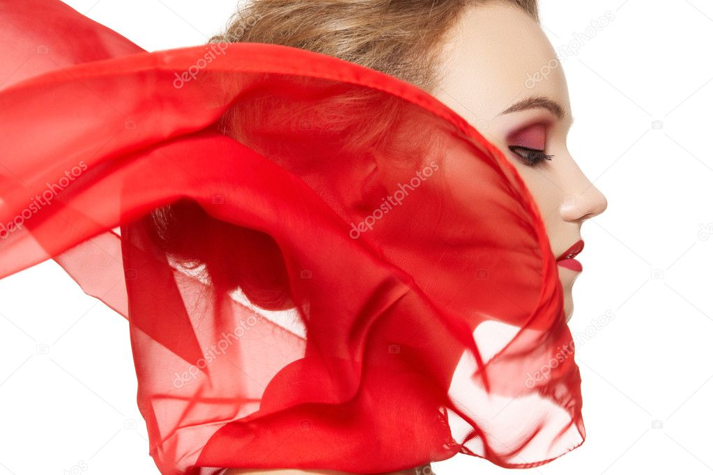 Fashionable portrait of a girl model with waving red silk scarf