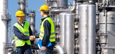 Two petrochemical contractors closing a deal in front of an oil refinary stock vector