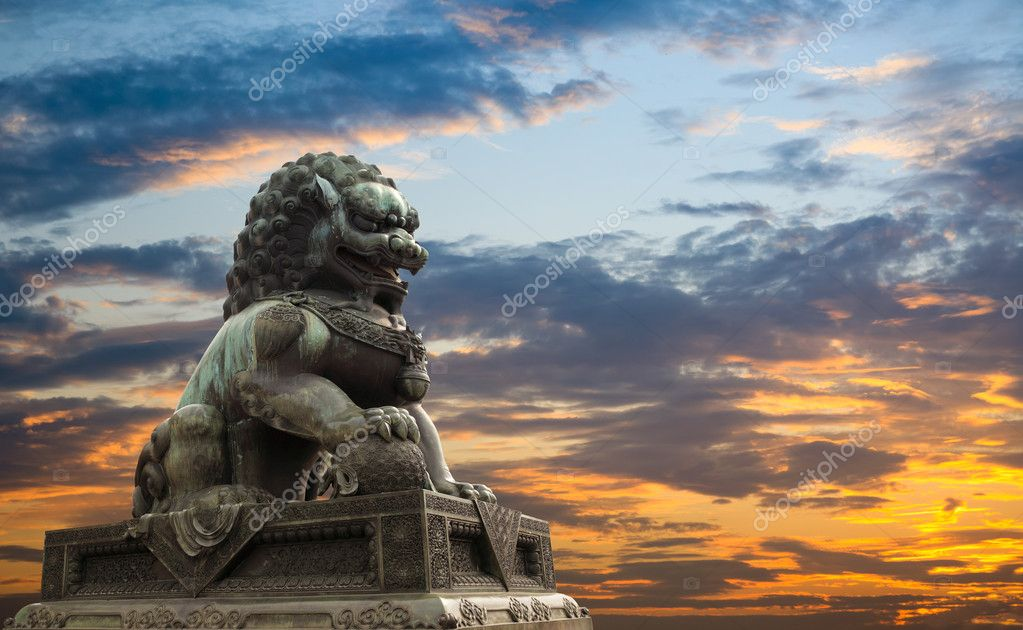 Majestic lion statue with sunset glow background