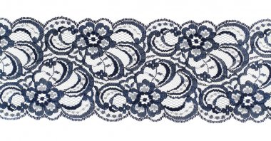 Lace trim ribbon over white. Embroidered fabric. Closeup