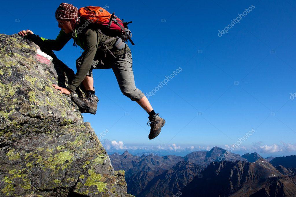 Young man climbing the mountain ridge stock vector