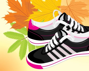 Pair of black sneakers on the autumn background