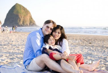 Small family with disabled little boy sitting at the beach by th