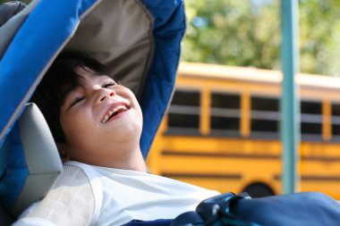 Disabled five year old boy in wheelchair outdoors by school bus