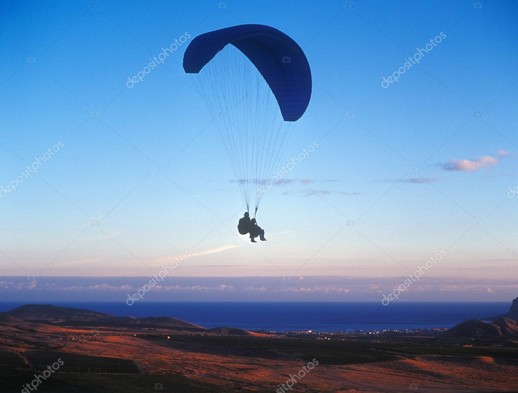 Tandem paragliding at sunset.